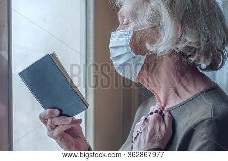 An Elderly Woman In A Medical Respiratory Mask Near The Window Prays With A Rosary, Cross And A Bibl