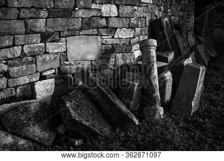 Gravestones Lit By Sun Placed Near A Wall And Abandoned.