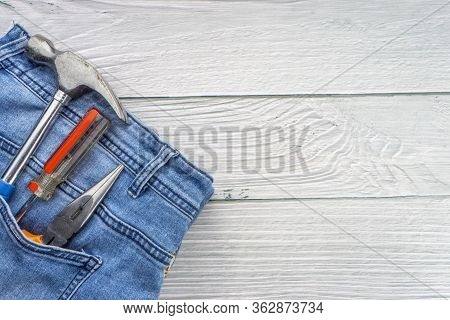 Jeans, Screwdriver, Hammer And Pliers On Wooden Background. Jeans Texture, Blue Denim Jeans With Too