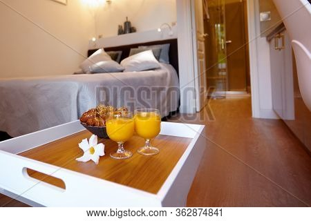 Breakfast Is On A Tray By The Bed In The Room. Fresh Pastries And Glasses Of Freshly Squeezed Juice