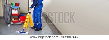 Professional Janitor Cleaning Office. Cleaner Using Broom At Workplace