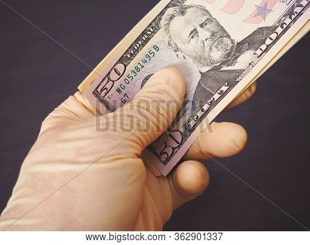 A Hand In A Flesh-colored Latex Glove Holds A Bundle Of American Us Money. Above Is A 50 Dollar Bill