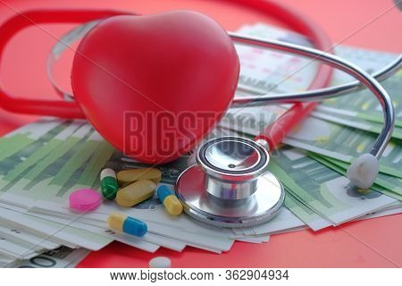 Close Up Of Cash, Pill And Stethoscope On Red Background