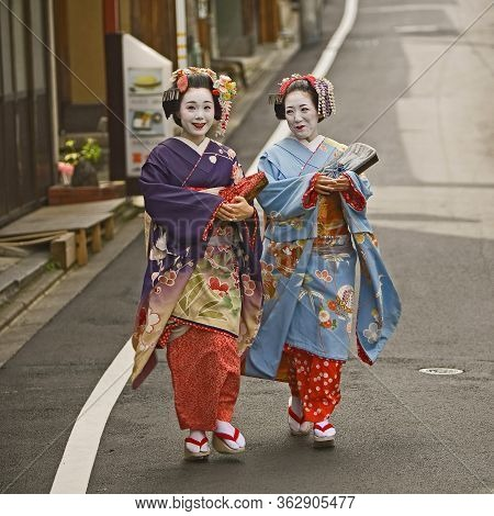 Kyoto - May 9 2010. Unidentified Geishas Walking By An Old Street And Speaking  In Gion District, Ky