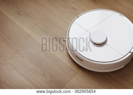 Robot Vacuum Cleaner Performs Automatic Cleaning Of The Apartment At A Certain Time. White Robot Vac