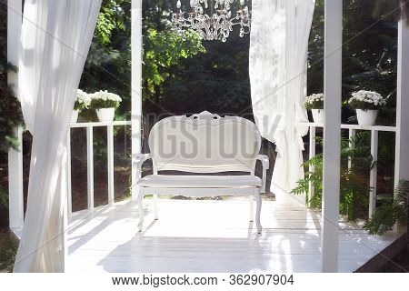 In The Garden There Is Terrace On Which A White Sofa In Style Of Provence Or Rustic. Beautiful Sofa