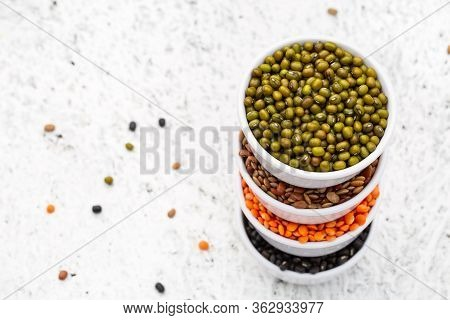 Indian Legumes - Mung Dal, Black Orid, Red Masoor Dal, Horse Gram In White Melamine Bowls On White B
