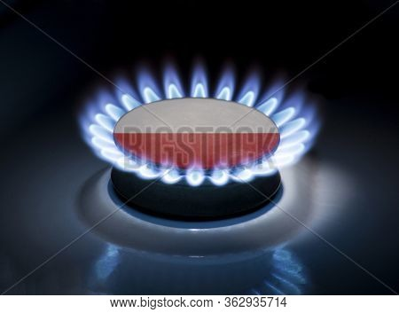 Burning Gas Burner Of A Home Stove In The Middle Of Which Is The Flag Of The Country Of Poland. Gas