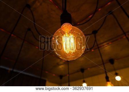 Close-up Of Big Vintage Incandescent Lights Bulb Hanging In A Dark Room. Decorative Edison Light Bul