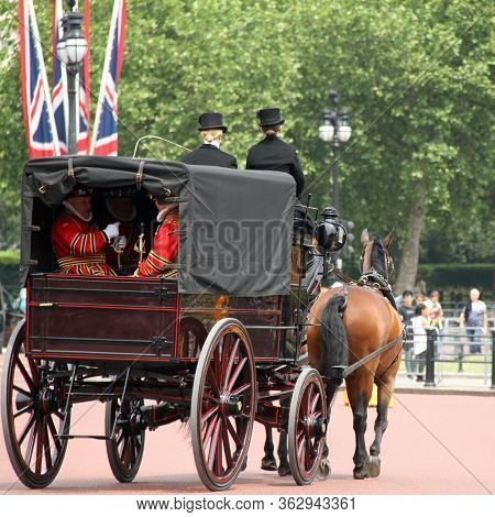 London - Jun 12: Horse And Carriage Exit Buckingham Palace With Yeomen Guards Known As Beefeaters.ta