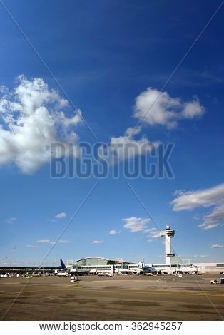 Transportation image of commercial passenger airplanes at airport gates over sunny blue sky