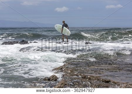The Surf Enters The Water. Male Surfer Entering The Sea With His Board In A Black Surfing Suit. Tene