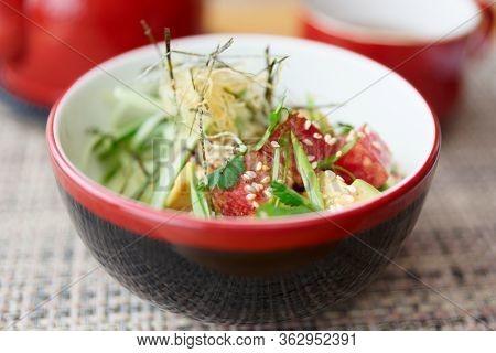 Poke bowl with raw tuna, avocado and seaweed, close-up