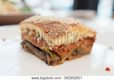 Slice of moussaka, traditional Greek and Balkan dish, on white plate, close-up