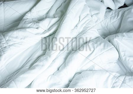 Top View Of White Blanket That Wrinkles On The Bed After Sleep In A Long Night.