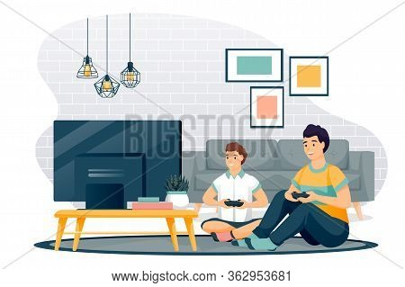 Happy Father And Son Play In Video Game. Dad And Little Boy With Gamepads Sit On Floor In Living Roo