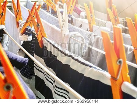 A Group Of Orange Clothes Pegs On A Drying Rack To Dry The Laundry. Clothes Hung Out To Dry Inside A