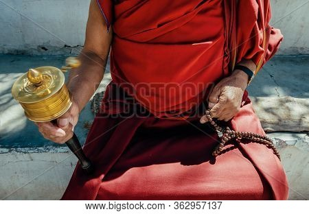 Hands Of A Tibetan Buddhist Monk With A Spinning Tibetan Prayer Wheel And Wooden Mala, In Ladakh, No