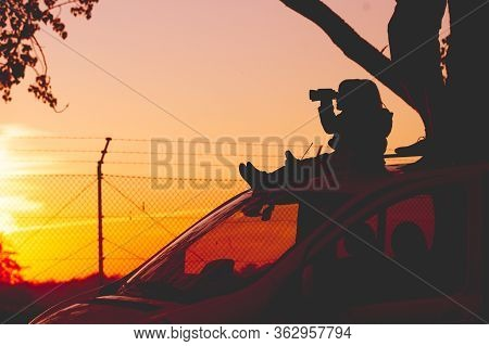 Man With Children On Car Roof Observing Something In The Distance Through Binoculars. Silhouette Aga