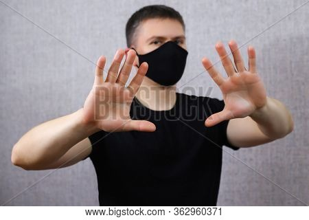 Young Man In A Black Medical Mask Shows His Hands Stop. Guy On A Light Background. Fear Of A Coronav
