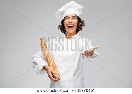 cooking, culinary and bakery concept - happy smiling female chef or baker in toque holding french bread or baguette over grey background