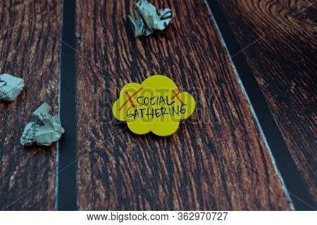 Social Gathering Write On A Sticky Note Isolated On Wooden Table Background