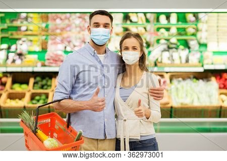 shopping, sale, consumerism and people concept - happy couple wearing face protective medical masks for protection from virus disease with food basket at grocery store or supermarket showing thumbs up