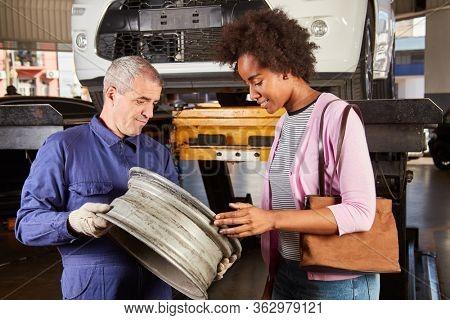 Car mechanic shows customer a broken car rim during inspection in the workshop