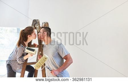 Couple in love painting and renovating in the new apartment or in the new home