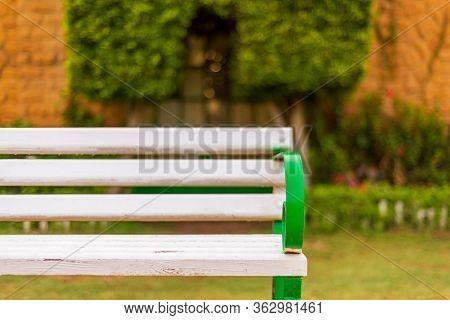 Wooden White Antique Garden Bench With Blurred Background Of Orange Stone Bricks Wall At Public Park