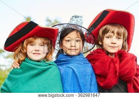 Three children in colorful fantasy costumes in carnival or children's theater