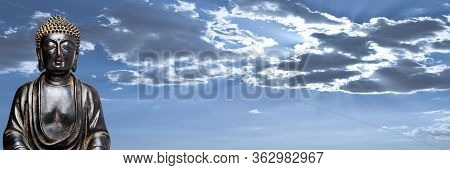 A View Of A Replica Statue Of The Buddha With A Dynamic, Cloudy Sky In The Background