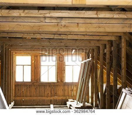 The Attic Of A Wooden House. View Of The Attic Windows Through Which Sunlight Falls.