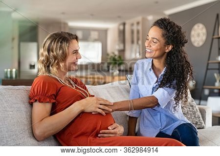 Cheerful african friend feeling belly bump of pregnant woman. Happy girl with hands on expecting mother's stomach feeling baby movement. Young woman talking to friend and touching her tummy at home.