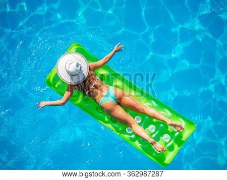 Woman on a lilo at the swimming pool