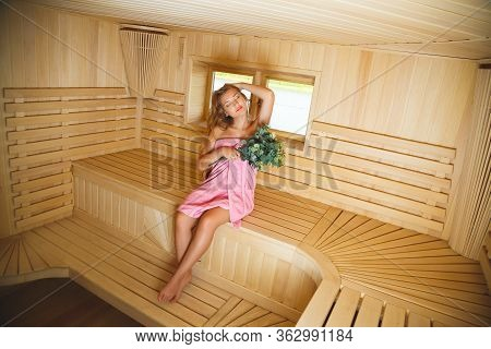 The Lovely Girl Sits In A Sauna Wrapped Up By A Pink Towel With A Bath Broom In A Hand