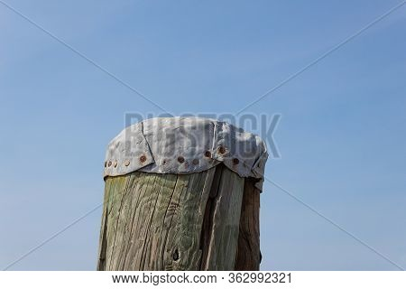Old Metal Piling Cap Hand Formed And Nailed Into The Top Of A Treated Wood Piling, Closeup, Horizont