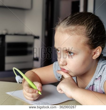 Portrait Of Serious Elementary School Girl Writing A Letter On A Sheet Of Paper With Pen In Hand Sit