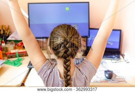 Young Girl Sitting At Home Desktop Computer, Raising Hands Up, Rear View. Back To School, Homeschool