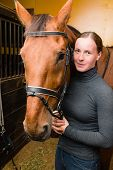 Woman bridle a horse in the stall poster