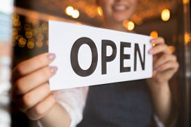 Hands of young waiter or owner of restaurant or cafe putting notice open on the door at the beginning of working day