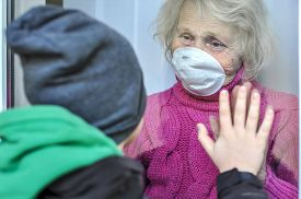 Grandmother In A Respiratory Mask Communicates With Her Grandson Through A Window. Elderly Quarantin