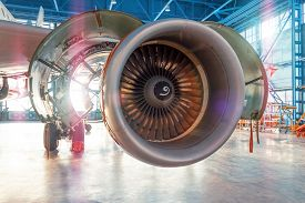 Industrial View Of An Airplane Engine With An Open Hood For Repair In Aviation Hangar, With Bright L