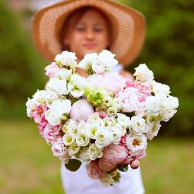 A Wonderful Large Bouquet Of White-pink Peonies In The Hands Of A Girl. A Child In A Straw Hat With