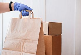 Courier Delivering Boxes And Bag. Hand Holding Bag With Food. Contactless Delivering Concept. Keep S