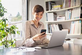 Businesswoman working on laptop sending a text message with phone in creative office. Happy smiling woman working sitting at desk. Successful architect enjoy the good news while working from home.