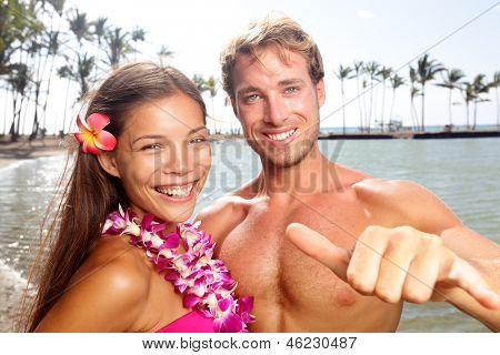 Hawaii couple happy on Hawaiian beach. Woman wearing flower lei garland and man giving shaka aloha hand sign on vacation travel. Portrait of multiracial couple ,asian mixed race woman, caucasian man poster
