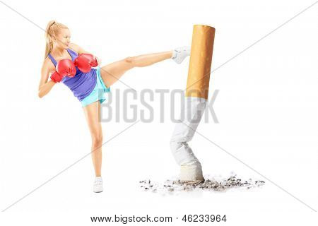 Full length portrait of a young female with boxing gloves kicking with her leg a cigarrette butt isolated on white background