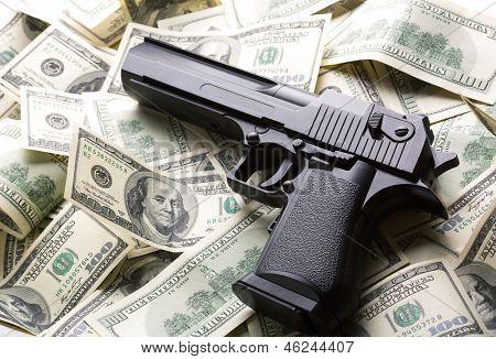 Heap of $100 dollar bills and handgun