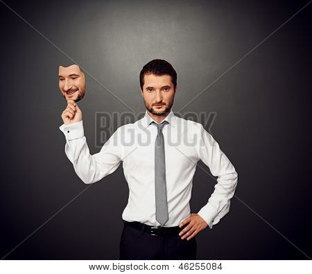serious businessman holding mask with good mood